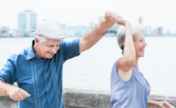 Älterer Mann und  ältere Frau haben Spaß draußen am Meer/Strand mit einer Stadt/Skyline im Hintergrund